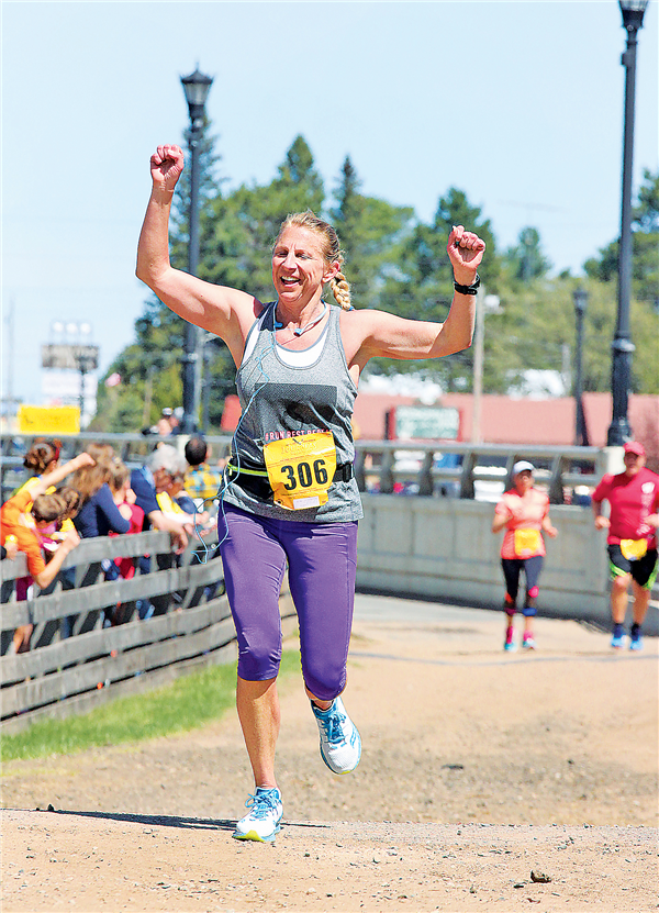 Kimberly Leupold of Milwaukee raising her arms as she finishes the half-marathon.