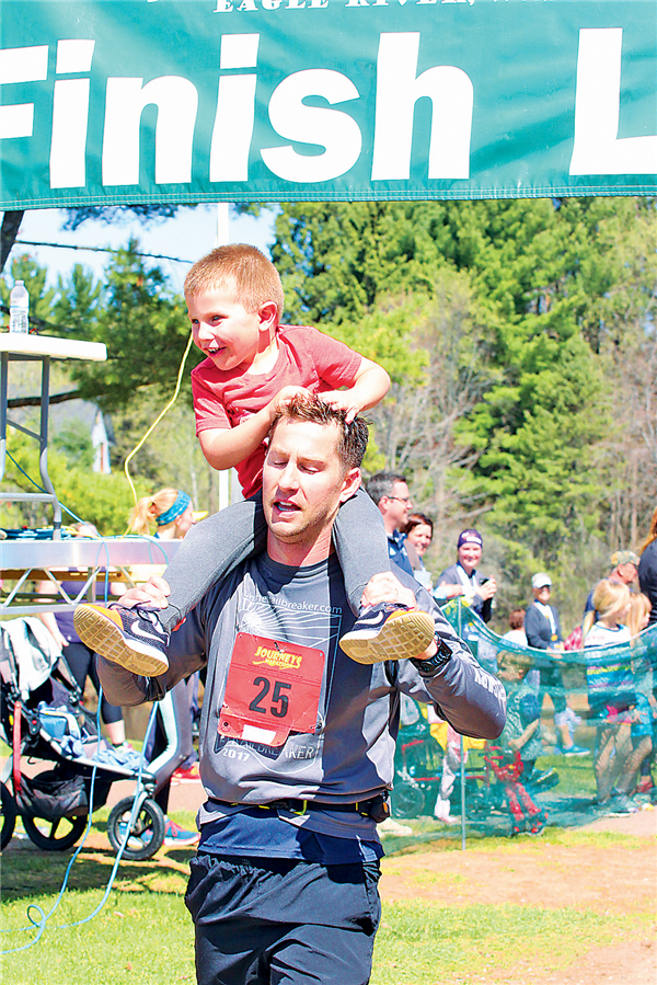 Overall marathon winner Kevin Kiser of Oconomowoc finishing the 26.2-mile race with his son on his shoulders.