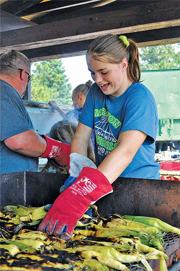 Emily Fink takes corn from the grill at the Three Lakes Firemen's Picnic held Sunday. —Staff Photo By DOUG ETTEN
