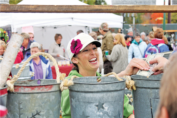 While the food is a big draw, it's the giant arts and crafts show with nearly 300 vendors that attracts the largest crowds to Cranberry Fest. This vendor selling maple sap pails was all smiles Saturday morning. —Staff Photos By GARY RIDDERBUSCH
