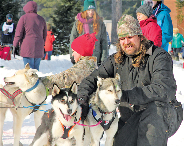 A musher from Alaska holding his team at the starting line.