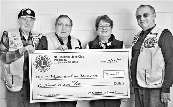 St. Germain Lions Club members took a break from putting candy in Easter eggs for the annual Easter egg hunt to pass along a $2,000 donation to the Marshfield Clinic Foundation. Taking part in the presentation are, from left, club Secretary Stan Rakowski, club President Fred Radtke, Marshfield Clinic's Kim Baltus and club first Vice President Rod Ingram. —Photo By Wally Geist
