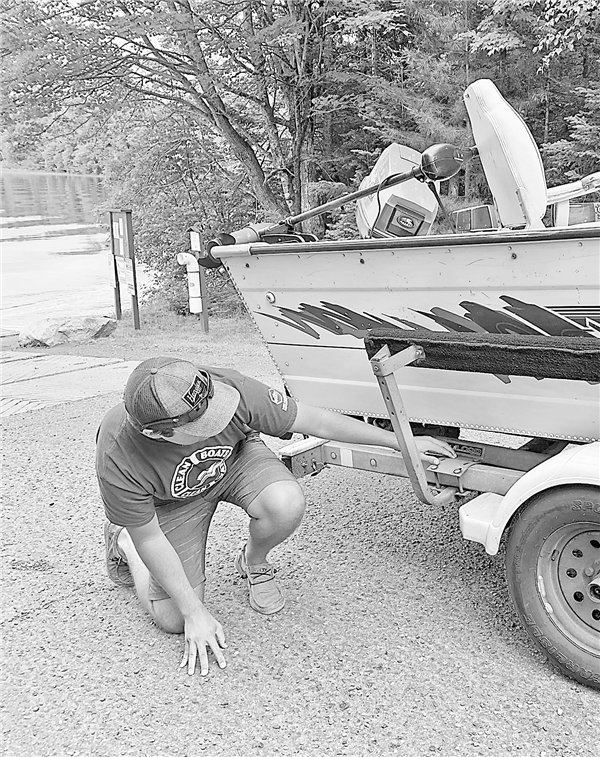 A worker with the Clean Boats Clean Waters program inspects a boat for milfoil and other exotics before it is launched. —Photo By The Author