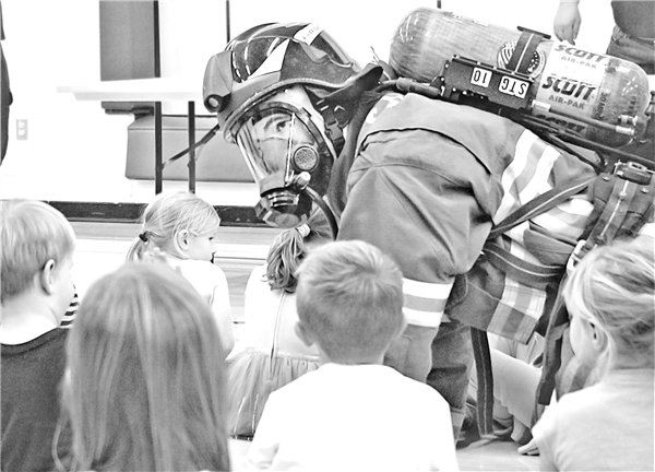 Firefighter and EMT Ryan Shelton donned his fire-fighting gear as a way of showing children not to be afraid if a firefighter comes to save them. Air pack breathing sounds and air pack warning tones were demonstrated to help children not be frightened by the otherworldly-looking gear. —Photos By Wally Geist