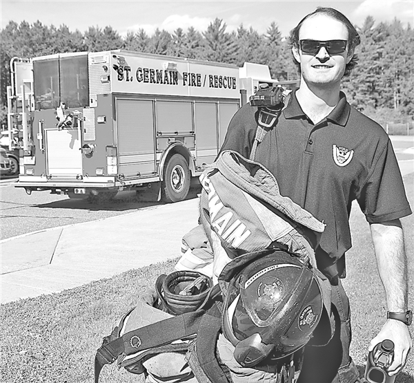 Ryan Shelton hauls his fire-fighting gear in to St. Germain Elementary School to teach students about fire safety as part of Fire Prevention Month.