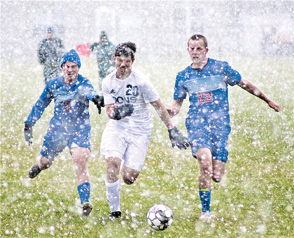 Northland Pines soccer players Trevor Romatoski (No. 3) and Bjorn Luebke (No. 22) surround Dons' defender Dillon Porter in the Division 4 Sectional final game played in the snow at Wisconsin Rapids Saturday. —Staff Photo By DOUG ETTEN