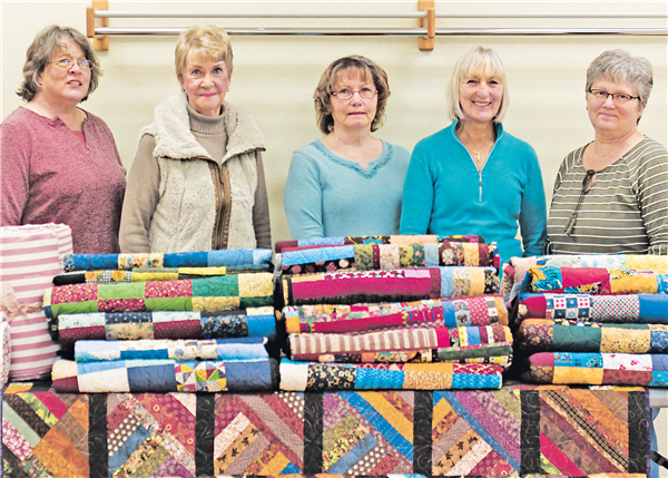 Members of the Kalmar Quilters pose here with about 25 quilts they made throughout the year and are donating to Sunshine for Humanity Homeless Shelter in Eagle River and the Tri-County Council on Domestic Violence and Sexual Assault Inc. Members are, from left, Joan Flaherty, Joyce Dumas, Sandy Tienhaara, Lynne VanDreel and Cheryl Breitenfeldt. —Staff Photo By MICHELLE DREW
