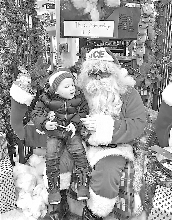 Bennett Brainard, 3, of Eagle River, visited with Santa at Nelson's Ace Hardware in Eagle River Saturday. —Staff Photo By GARY RIDDERBUSCH