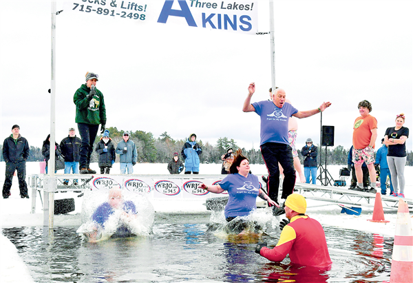 Three brave plungers hit the frigid water of Spirit Lake in Three Lakes during the 20th annual Polar Bear Plunge for Angel On My Shoulder. —Photo By Kerry Griebenow