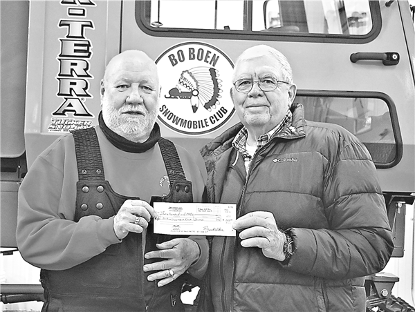 Bo-Boen President-elect Bob Ausloos (left) receives a check for $500 from Bruce Weber. Weber's businesses benefit from the snowmobile industry in St. Germain, with the family's Little Saint Mobil Express benefiting directly from fuel sales and St. Germain Sentry benefiting indirectly from visitors purchasing groceries and other products carried by the store. Weber believes that most businesses benefit greatly from the activity. —Photo By Wally Geist